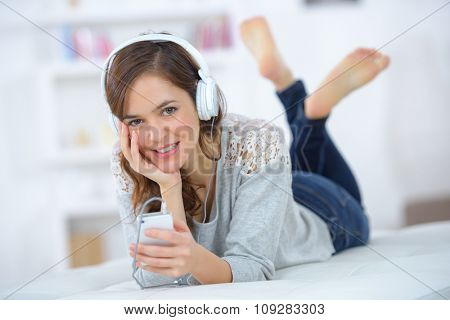 Lady layed on front, listening to mp3 player