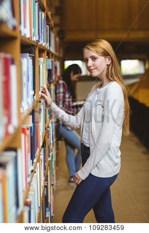 Blond student looking for book in library shelves at the university