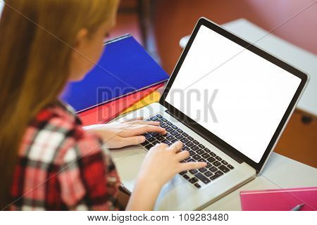 Blonde student using laptop during class at the university