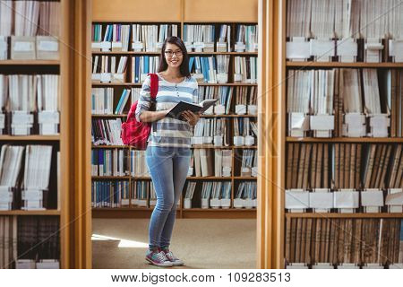 Pretty student with backpack reading a book in library at the university