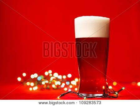 Full glass of bear or ale with christmas lights on red background