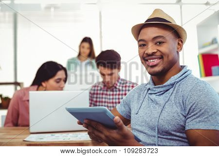 Young creative worker smiling at camera in casual office