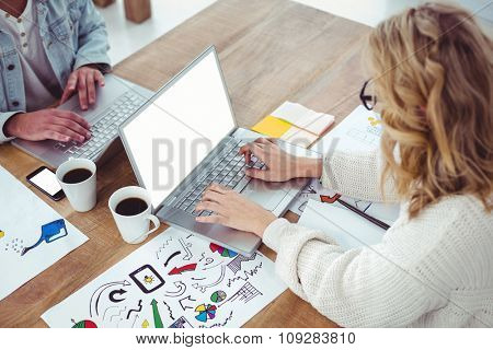 Creative businesswoman working on her laptop in casual office