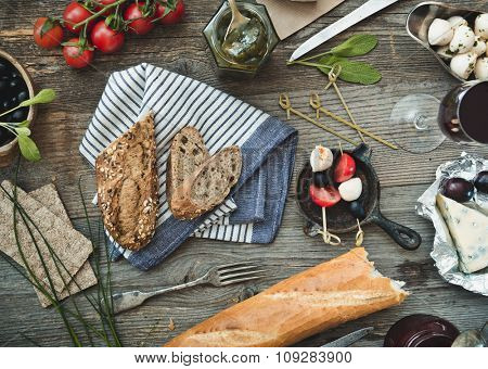 French snacks on a wooden background. Cheese, wine and other ingredients on a wooden table