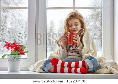 little girl sitting by the window with a cup of hot drink