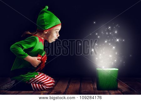 Cute little girl opening a magic gift box.