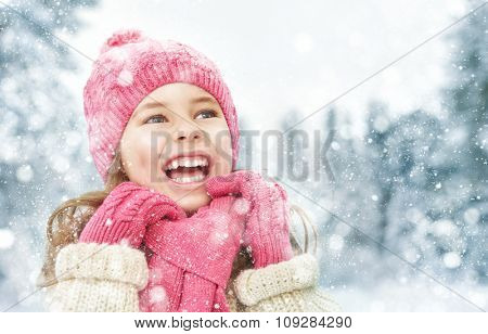 Happy child girl playing on a winter walk in nature
