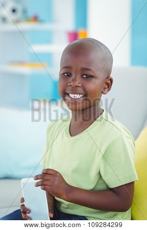 Happy boy using a smartphone on the couch
