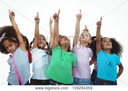Line of girls standing with hands pointing up against a white background
