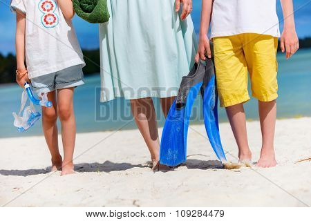 Close up family of mother and kids with towel and snorkeling equipment enjoying vacation at tropical beach