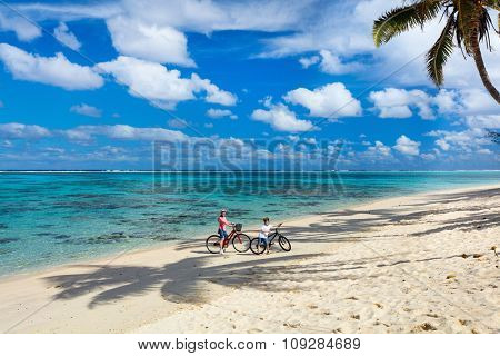 Family of mother and son biking at tropical beach having fun together