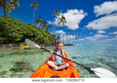 Little girl enjoying paddling in colorful orange kayak at tropical ocean water during summer vacation