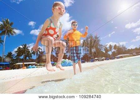 Beautiful tropical beach with happy kids splashing at shallow water on foreground having fun on vacation. Focus on beach