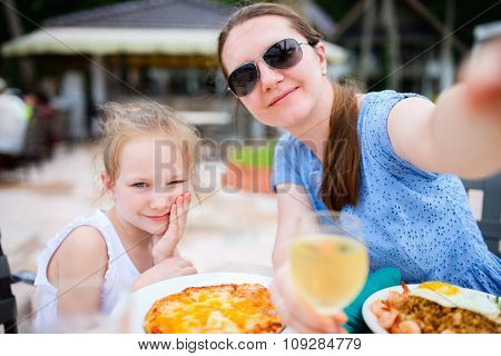 Happy mother and her adorable little daughter at outdoors restaurant taking selfie while having delicious lunch