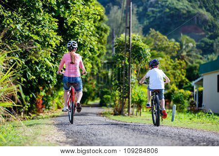 Family of mother and son biking at tropical settings having fun together riding bikes
