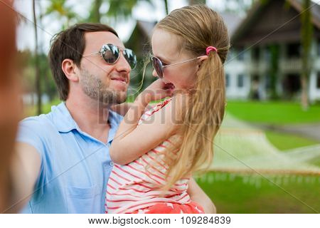 Happy family father and his adorable little daughter on vacation taking selfie