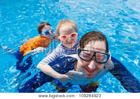 Happy family father and his adorable kids at outdoors swimming pool