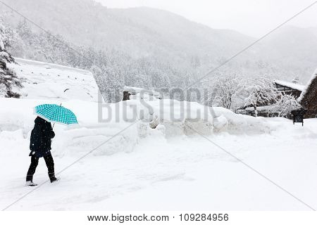 Back view of a tourist at historic Japanese village Shirakawa-go at winter, one of Japan's UNESCO world heritage sites