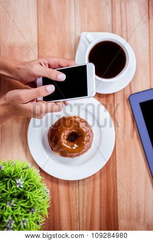 Overhead of feminine hands using smartphone with tablet, coffee and donut on table