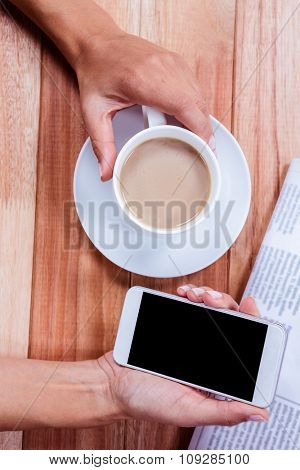 Part of hands holding coffee and smartphone on wooden desk