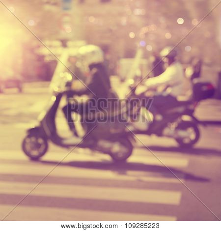 Motorcycle riders on the street in motion blur during sunset.