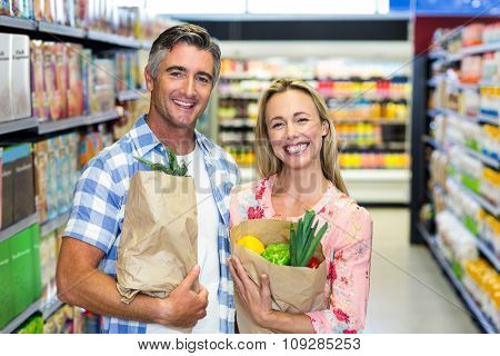 Smiling couple with grocery bags at the supermarket