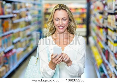 Smiling woman using smartphone in supermarket