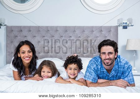 Portrait of smiling family laying on the bed at home