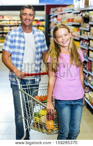 Portrait of smiling father and daughter at the supermarket