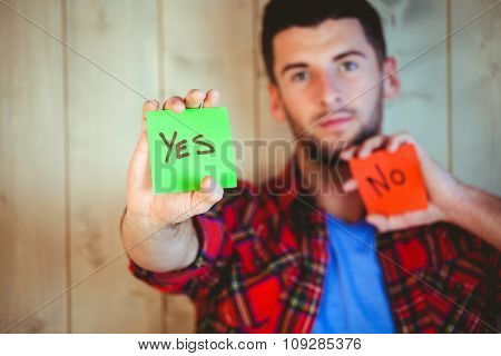 Handsome hipster showing yes and no cards against wooden background
