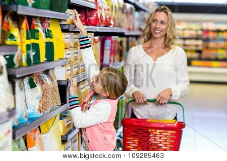 Cute daughter taking food from shelf in supermarket