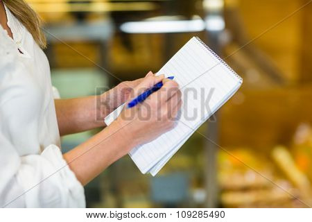 Woman hands checking list at supermarket