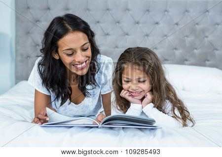 Happy mother and daughter reading a book on the bed at home