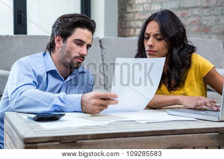 Couple sitting on the floor in living room paying bills