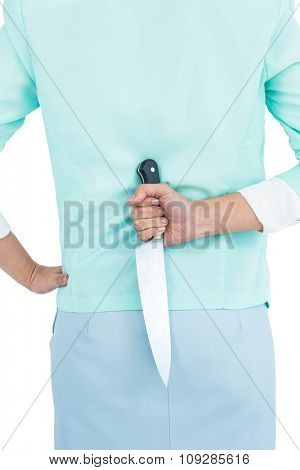 Rear view of businesswoman hiding knife in her back against white background