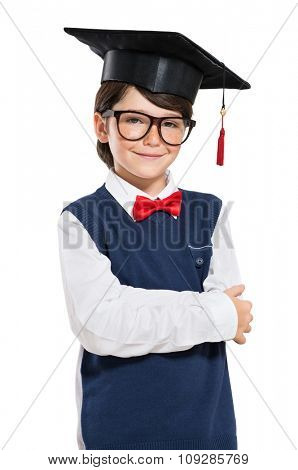 Closeup of smiling boy wearing mortarboard isolated on white background. Portrait of proud little student looking at camera. Happy cute male child wearing graduation hat and eyeglasses.