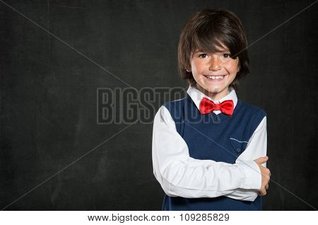 Closeup shot of little boy standing with armcrossed isolated on blackboard. Smiling cute male child with red papillon looking at camera. Lovable boy wearing waistcoat and red bow tie with copy space.