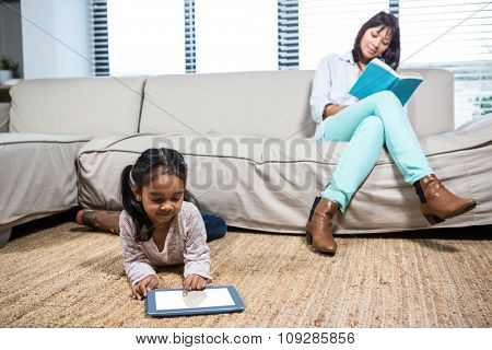 Happy mother reading book while her daughter using tablet in living room