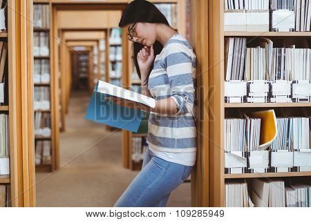 Focused student leaning against bookshelves and reading a book in library at the university