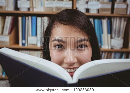 Smiling student hiding face behind a book at the university