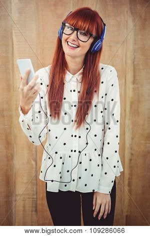 Attractive hipster woman listening to music with headphones against wooden background