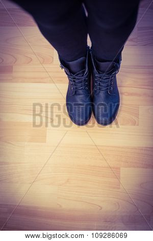 Cropped image of woman wearing boots on parqueting floor
