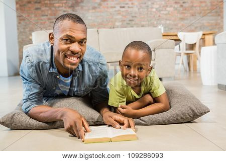 Father and son reading on the floor in living room