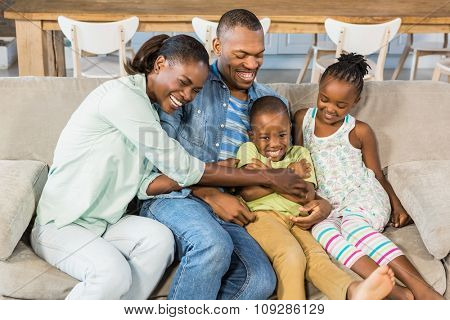 Happy family posing on the couch together in living room