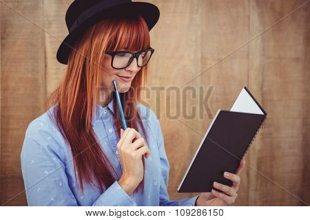 Smiling hipster woman writing notes against wooden background