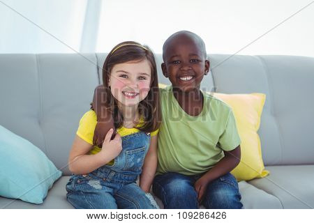 Smiling girl and boy together on the couch