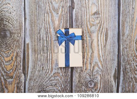 Gift box with blue ribbon on dark wooden background
