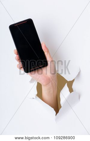 Hand through the hole in paper with cellphone