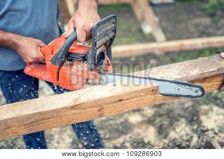 Workers Using Chainsaw Cutting And Sawing Industrial Construction Wood. Laborer Slicing Timber