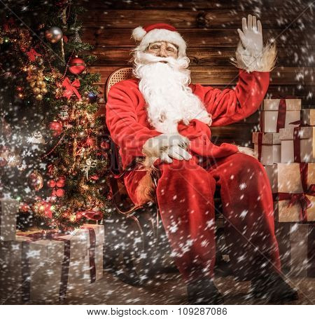 Santa Claus sitting on rocking chair in wooden home interior with gift boxes around him